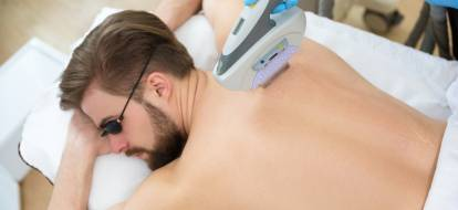 laying men while laser hair removal treatments black