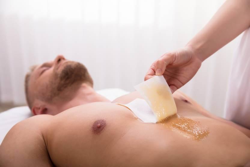 leżący mężczyzna podczas wylewania wosku do depilacji na klatkę piersiową