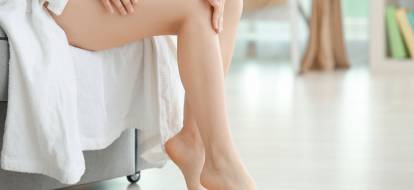 woman's legs on background with white towel