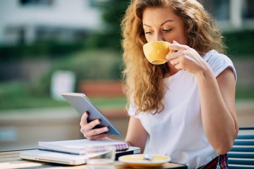 kobieta trzymająca tablet popijająca kawę zżółtej filiżanki wkawiarni